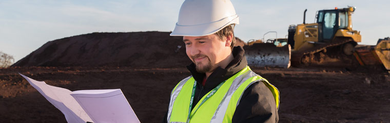 Person wearing a hard hat on a building site, looking at planning documents