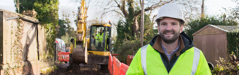 Person wearing a hard hat stood by a digger